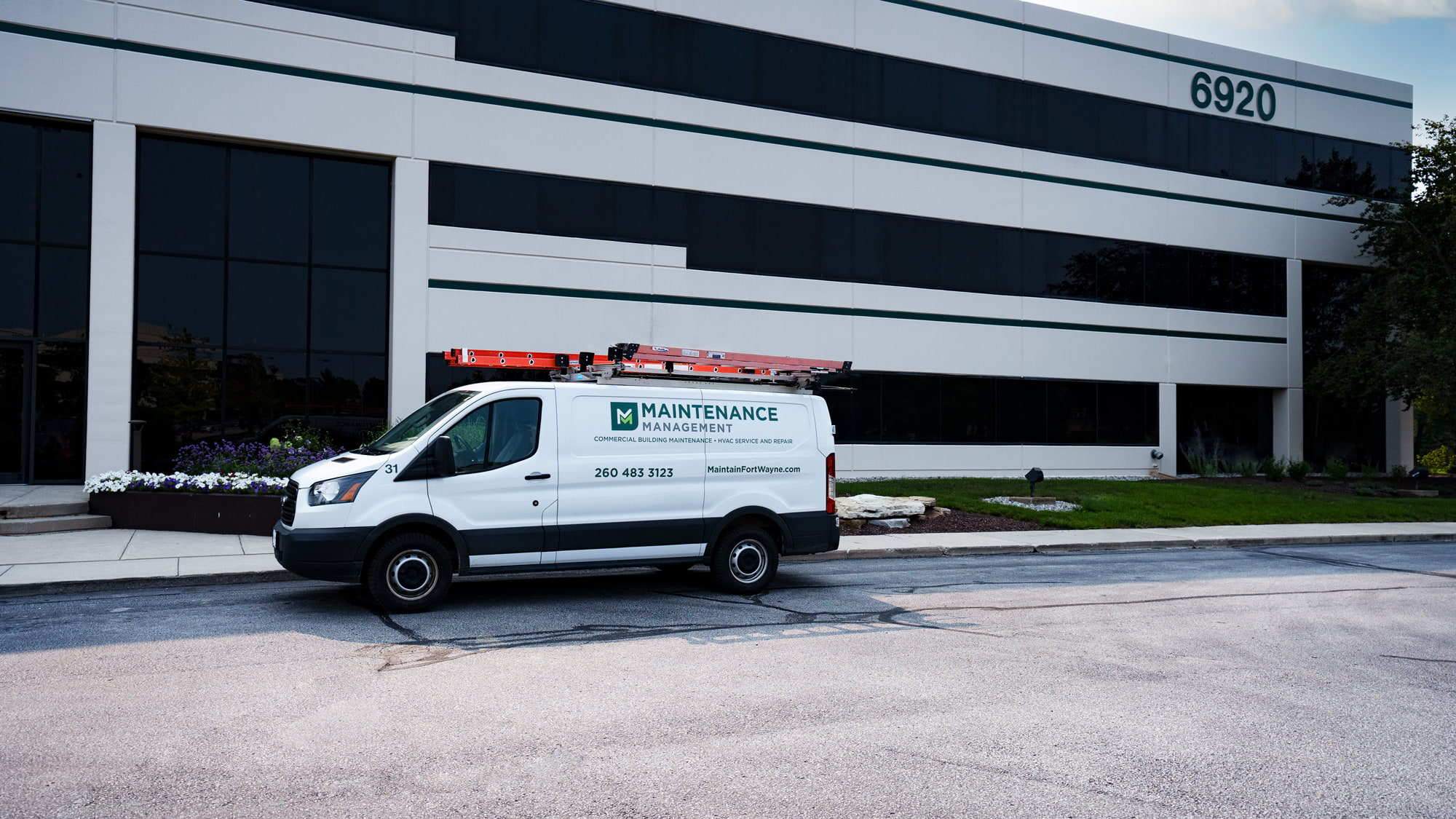 Maintenance Management outsourcing maintenance and HVAC service van in front of multi-tenant office building.
