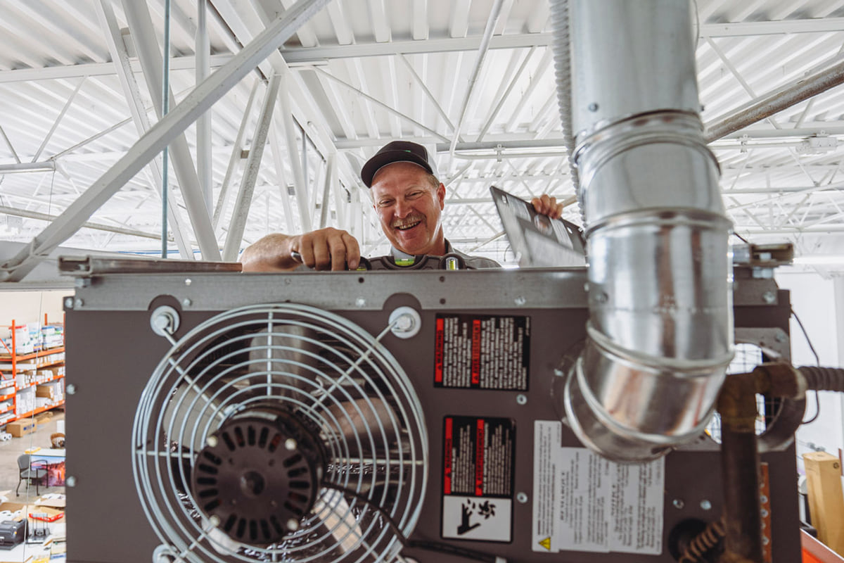 Maintenance technician repairing a hanging heating unit in warehouse space.